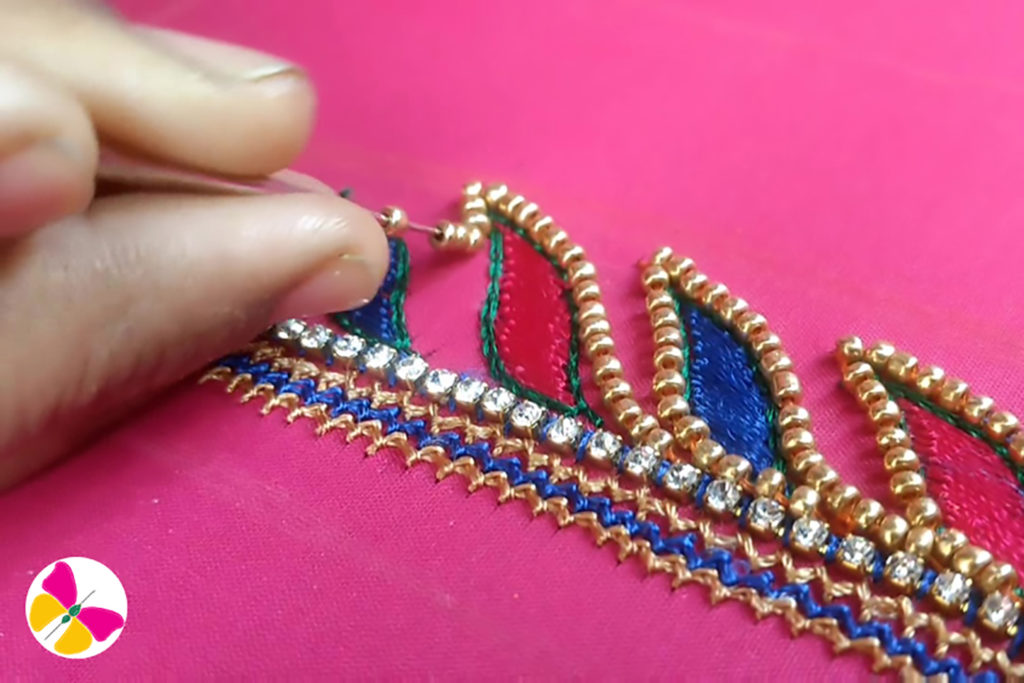Stitching gold beads to the leaf outline